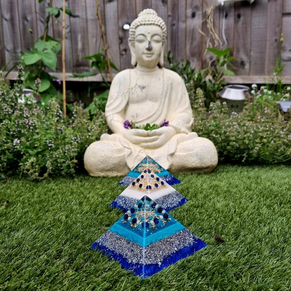 orgonite pyramids in front of meditating Buddha