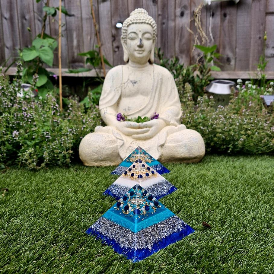 orgonite pyramids in front of meditating Buddha